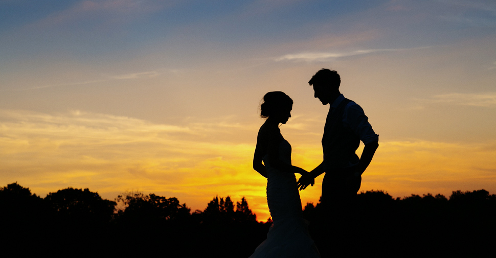 Silhouette of couple against sunset background at wedding in Dulwich